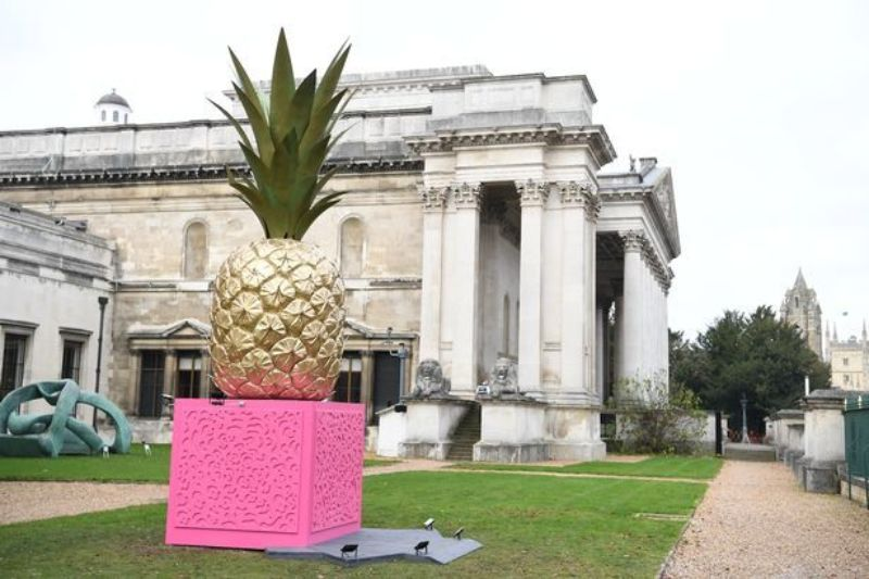 The Fitzwilliam Museum, Cambridge, with Bompas & Parr's Giant Architectonic Pineapple with its pink Fibonacci-sequence-inspired base celebrating the multi-sensory aspects of the pineapple and the Museum's links to the first pineapple cultivation in Britain; displayed on the front lawn to encourage the public inside to visit the Feast & Fast exhibition as well as the permanent collections.